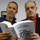 Journalists Gerard Davet and Fabrice Lhomme pose with a copy of their book on French president Francois Hollande (AP)
