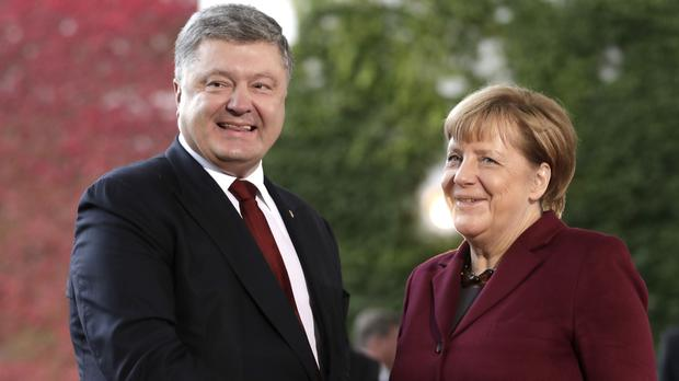 German chancellor Angela Merkel welcomes Ukraine's president Petro Poroshenko to the Berlin summit (AP)