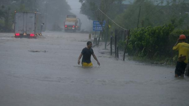 A man wades through a flooded highway at the height of Super Typhoon Haima (AP)