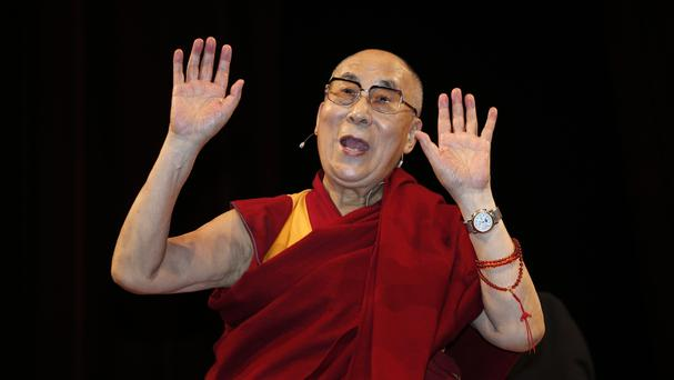 The Dalai Lama acknowledges the crowd at the Arcimboldi Theatre, where he was conferred with the honorary citizenship of Milan (AP)