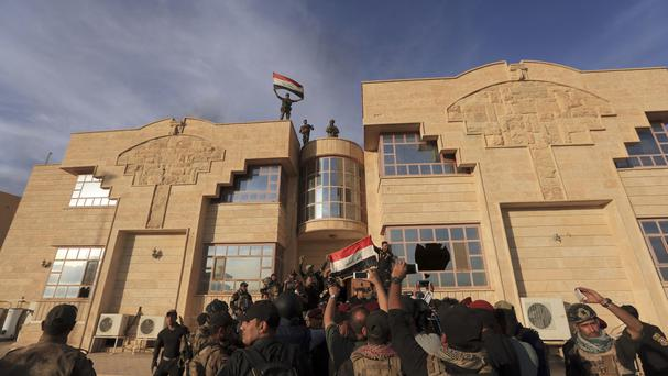 Iraqi special forces raise an Iraq flag after retaking Bartella, outside Mosul (AP)