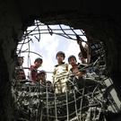 Boys look through a hole made by a Saudi-led air strike on a bridge in Sanaa, Yemen (AP)