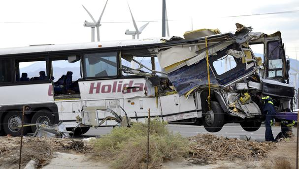 Workers prepare to move the wreckage of the tour bus (AP)