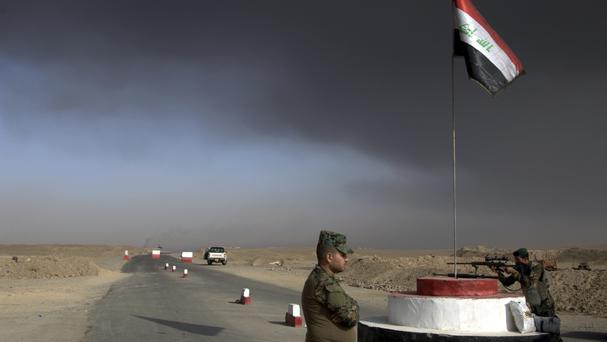 Iraqi troops guard a checkpoint near the village of Awsaja, Iraq (AP)