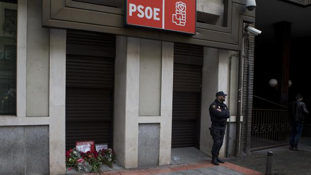 Red roses, a Spanish socialist symbol, lie outside the socialist headquarters as a protest gesture while a police officer stands guard in Madrid (AP)