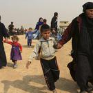 Civilians leave their homes as Iraq's elite troops fight against Islamic State militants in the village of Tob Zawa (AP)