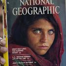 Inam Khan, owner of a bookshop in Islamabad, Pakistan, shows a copy of a magazine with the photograph of Afghan refugee Sharbat Gulla (AP)