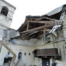 The Church of San Sebastiano stands amid damaged houses in Castelsantangelo sul Nera, Italy (AP)