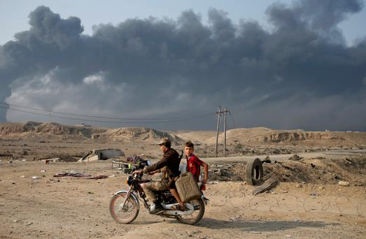Armed members of Shi'ite militia Hashid Shaabi ride a motorbike near Qayyara, south of Mosul, Iraq October 27, 2016. Smoke in the background is from burning oilfields set ablazed by Islamic State fighters.