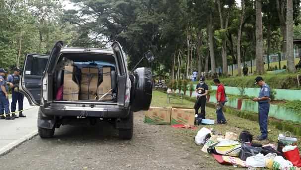 Residents watch as police inspect the contents of vehicles in the southern Philippines (AP)