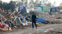 A migrant walks past debris from makeshift shelters during the dismantlement of the camp called the
