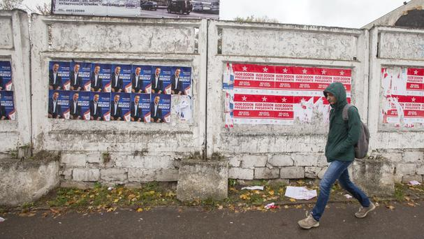 A woman walks by electoral posters in Chisinau, Moldova. (AP)
