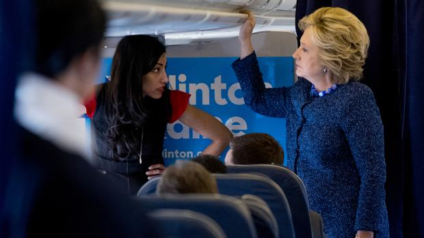 Hillary Clinton speaks with senior aide Huma Abedin on her campaign plane at Westchester County Airport in White Plains (AP)