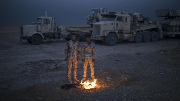 Iraqi army soldiers warm themselves next to a fire near the Qayara air base, south of Mosul (AP)
