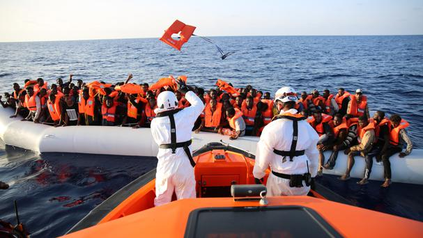 Lifejackets are thrown to migrants on a rubber dinghy rescued by the vessel Responder in the Mediterranean sea (AP)