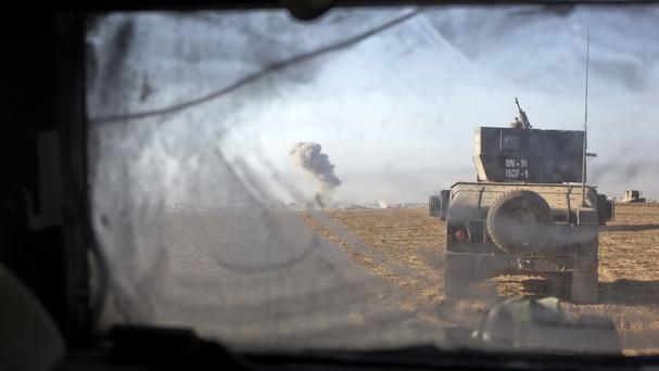 Iraqi special forces vehicles move as an air strike hits an Islamic State militant position in the distance (AP)