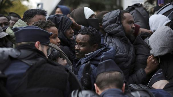 Migrants scramble to board buses to temporary shelters as police clear out hundreds of migrants camping out in northern Paris (AP)