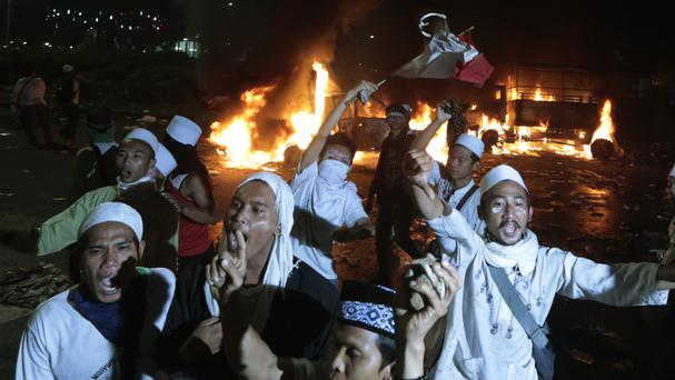 Muslim protesters chant slogans during a clash with police outside the presidential palace in Jakarta (AP)