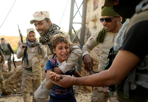 A boy reacts as Iraqi soldiers help him to walk out the front line during a battle with Islamic State in the Intisar disrict of eastern Mosul, Iraq. Photo: Reuters