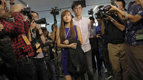 Newly-elected Hong Kong MPs Yau Wai-ching and Sixtus Leung are surrounded by photographers outside the legislature council (AP)