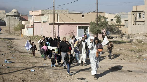 People displaced by fighting between the Iraqi military and Islamic State militants pass through an alley in Gogjali, on the eastern outskirts of Mosul (AP)