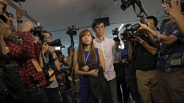 Yau Wai-ching, centre left, and Sixtus Leung, centre right, are surrounded by photographers outside the legislature council in Hong Kong. (AP)