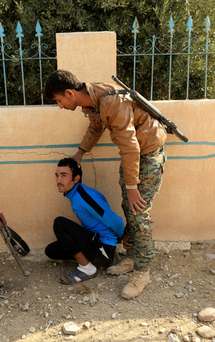 An Iraqi soldier with a man suspected of being a member of Isil, outside Mosul. Photo: Reuters