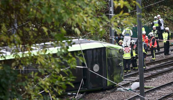 Members of the emergency services work next to the tram in Croydon, south London, yesterday after it overturned, killing at least seven and leaving other passengers trapped. Photo: Reuters/Neil Hall.