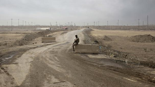 An Iraqi army soldier sits at a checkpoint in Qayara, south of Mosul. (AP)