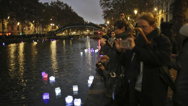 People place colourful lanterns into the Saint-Martin canal (AP)