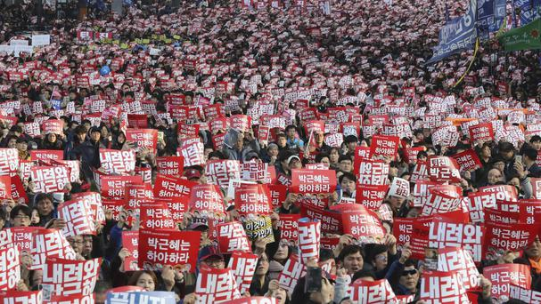 Protesters hold up cards during a rally calling for South Korean President Park Geun-hye to step down in Seoul on Saturday (AP)
