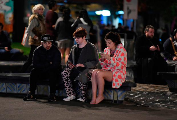People evacuated from buildings along Dixon Street check their mobile phones while sitting on a bench in Wellington after a 6.6 earthquake based around Cheviot in the South island shock the capital, New Zealand. Photo: Ross Setford/SNPA via AP
