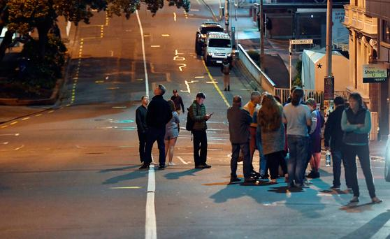 People evacuated from the Quest On the Terrace Hotel gather outside the hotel. Photo: Ross Setford/SNPA via AP
