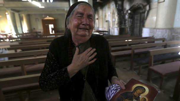 A Christian Iraqi woman cries at the St Addai church which was damaged by Islamic State fighters during their occupation of Keramlis village (AP)