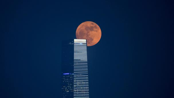The moon is seen with the International Commerce Centre building in Victoria Habour in Hong Kong (AP)
