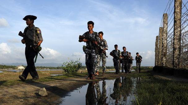 Burma police officers patrol along the border fence in Maungdaw, Rakhine State. (AP)