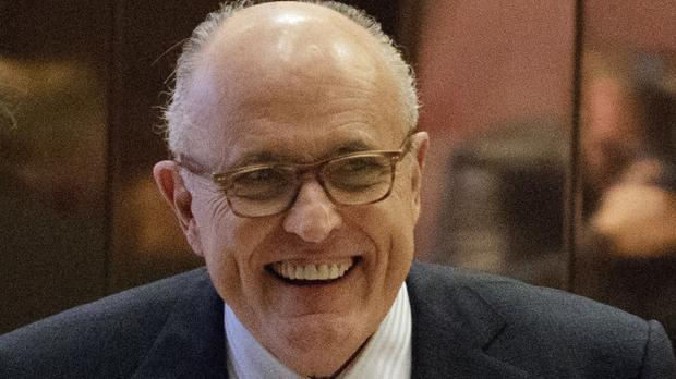 Former New York mayor Rudy Giuliani smiles as he leaves Trump Tower (AP)