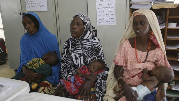 Mothers with malnourished children wait for treatment at a clinic in Maiduguri (AP)