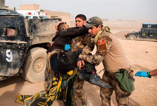 Frontline medics help carry an Iraqi soldier hit by sniper fire in his pelvis area out of their vehicle at an Iraqi Special Forces 2nd division outdoor field clinic in the Samah neighbourhood of Mosul. Photo: AFP/Getty Images