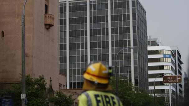 An emergency worker patrols a cordon in Wellington after officials determined a nine-storey office building, centre, is in danger of collapsing (AP)
