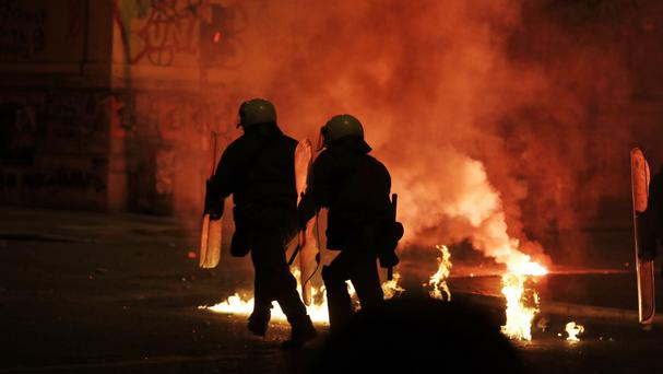 Greek riot police officers run through a blaze lit by a firebomb thrown by protesters during clashes in Athens (AP)