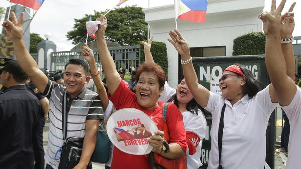Supporters of the former Philippine dictator Ferdinand Marcos cheer as they stand outside the Hero's Cemetery where he was buried in Taguig, south of Manila (AP)