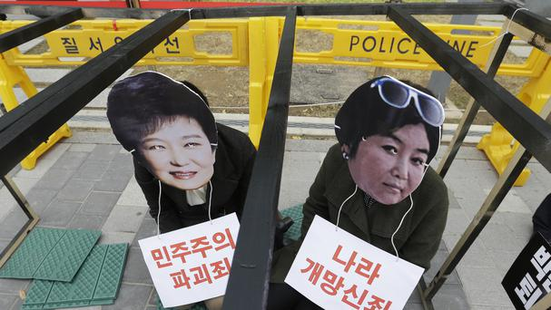 South Korean protesters wearing masks of president Park Geun-hye, left, and Choi Soon-sil, who is at the centre of a political scandal (AP)