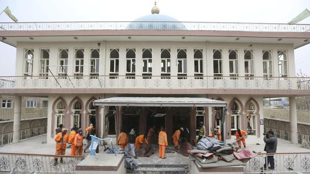Afghan municipality workers sweep Baqir-ul Ulom mosque after a suicide attack in Kabul (AP)