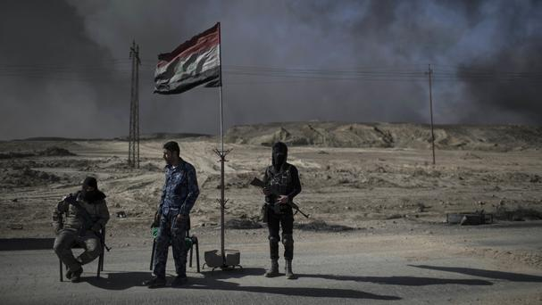 Guards at a checkpoint near burning oil fields in Qayara, south of Mosul (AP)