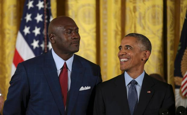 U.S. Presient Barack Obama smiles at retired NBA basketball Hall of Famer Michael Jordan (L) before awarding Jordan the Presidential Medal of Freedom during a ceremony in the White House East Room