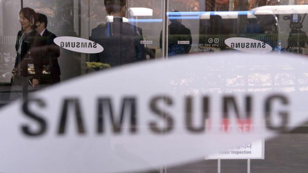 Employees walk past logos of Samsung Group at its headquarters in Seoul (Newsis/AP)