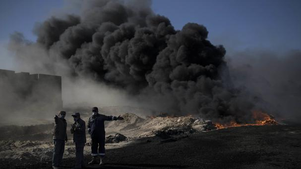 Oil workers try to extinguish burning oil fields in Qayara, south of Mosul, Iraq (AP )