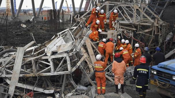 Rescue workers look for survivors after a work platform collapsed at the Fengcheng power plant in eastern China's Jiangxi Province (Xinhua/AP)