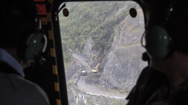 New Zealand prime minister John Key looks down from a military helicopter at work being done to clear a road (Iain McGregor/Christchurch Press/Pool via AP)